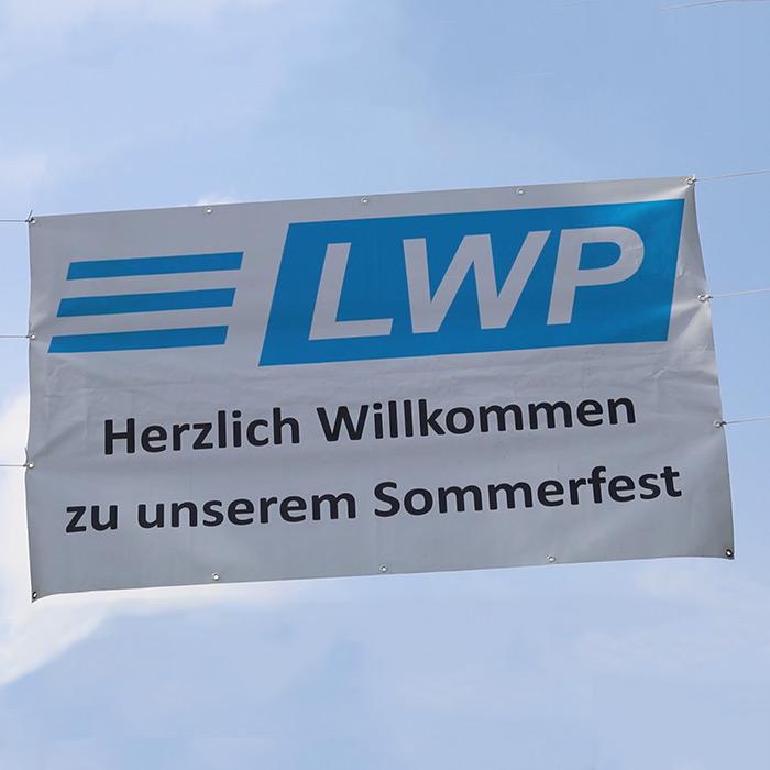 """Ein Banner mit der Aufschrift """"Herzlich WIllkommen zu unserem Sommerfest""""."""